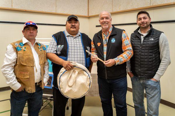 Kaska drummers present Premier Horgan with a Kaska drumstick